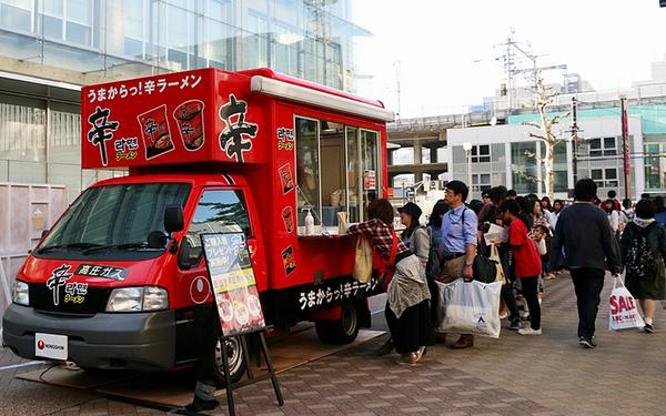"Japanese consumers wait in line to grab a taste of Nongshim's instant noodle Shin Ramyun. The company has been arranging tasting events across the country by setting up a ""kitchen car."" [Photo provided by Nongshim Co.]"