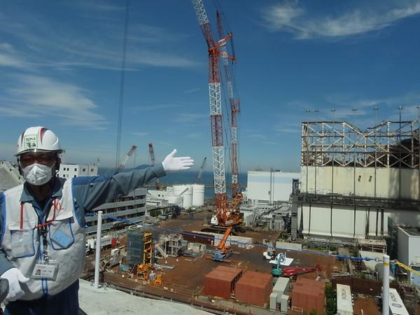 A Tokyo Electric Power official explains ongoing clean-up efforts to limit radioactive contamination from the nuclear reactors in front of the Fukushima Daiichi Nuclear Power Plant where hydrogen explosions damaged the buildings after the earthquake and tsunami on 11 March 2011. [Photo by Fukushima Joint Coverage Team]