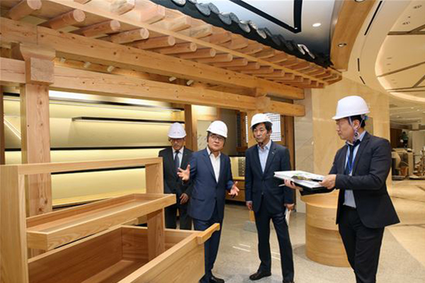 Chang Seon-wook (second from left), head of Lotte Duty Free, monitors the site before the grand opening of Lotte World Tower.