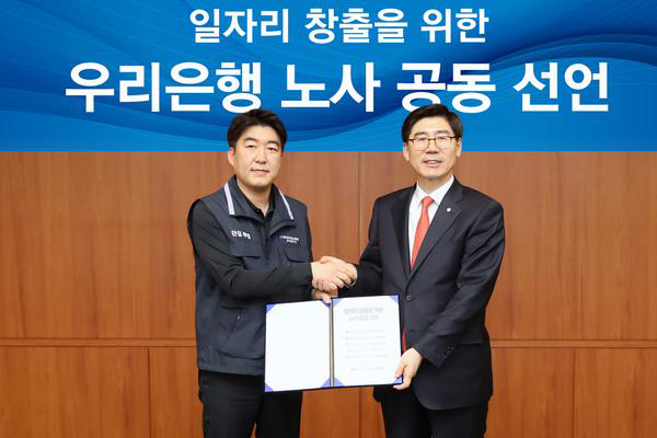 Lee Kwang-goo, chief executive and president of Woori Bank Co., right, poses with Park Pil-joon, head of the bank's labor union, after announcing joint plans to create new jobs and improve working environment. [Photo provided by Woori Bank]