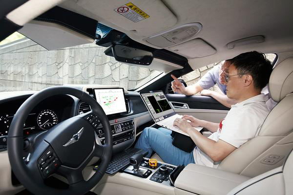 SK Telecom's vehicle technology research team and a team of researchers at Seoul National University (SNU), led by Professor Lee Gyung-soo, check the software of an autonomous car. [photo by SK Telecom]
