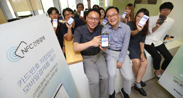 Hwang Seung-ik, chief executive of Hankook NFC, front left, and employees present the company's phone-to-phone payment module called Pay App. [Photo by Lee Chung-woo]