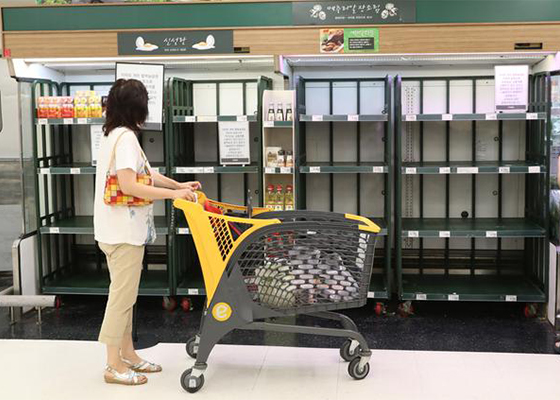 A customer is looking at empty egg shelves at one of Korea's major discount store chain. [By Lee Chung-woo]