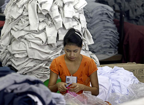 A Myanmar girl works among piles of clothes at the Shweyi Zabe garment factory in Shwe Pyi Thar Industrial Zone in Yangon. Garments are among Myanmar's largest exports.