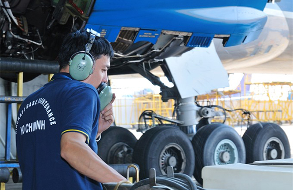 A technician is maintaining an aircraft at the Nội Bài International Airport.