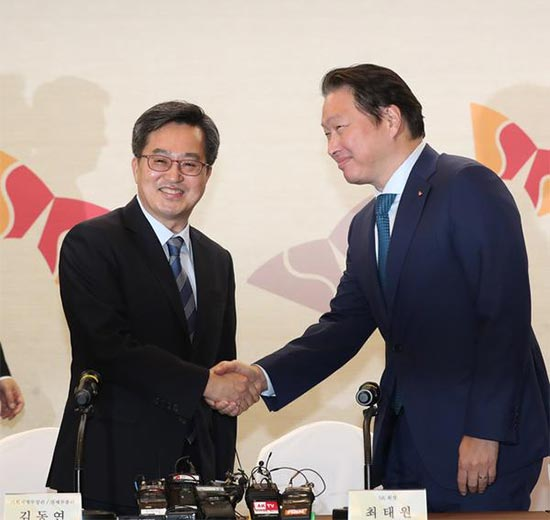 (From left) Finance Minister Kim Dong-yeon shakes hands with Chey Tae-won, chairman of SK Group.
