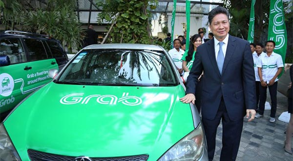 Transport Minister Sun Chanthol stands next to a Grab car at the company`s Phnom Penh launch event in December.
