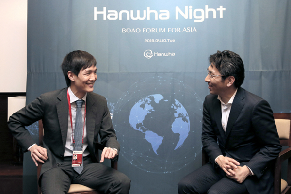 "Kim Dong-won (left), chief innovation officer of Hanwha Life, talks with Takashi Okita, CEO of SBI Ripple Asia, a Japan-based crytocurrency and blockchain company, at the ""Hanwha Night"" event held on the sidelines of the Boao Forum in Boao, China, Tuesday. [Photo provided by Hanwha Group]"