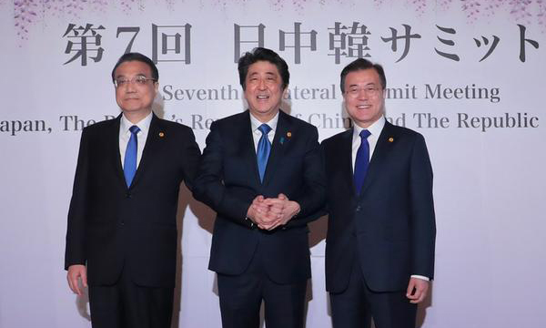 (From right to left) South Korean President Moon Jae-in, Japanese Prime Minister Shinzo Abe, and Chinese Premier Li Keqiang are holding hands at a trilateral summit in Tokyo on Wednesday. [Photo by Kim Jae-hoon]