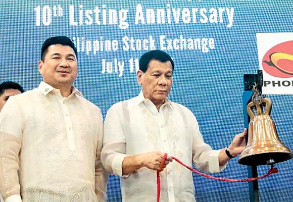 Philippine President Rodrigo Duterte, right, attends the tenth anniversary of the listing of Phoenix Petroleum Philippines Inc., an independent oil company founded by Dennis Uy, chairman and chief executive of Udenna Corporation, at the Philippine Stock Exchange on July 11, last year. [Photo provided by Philippine Information Agency]