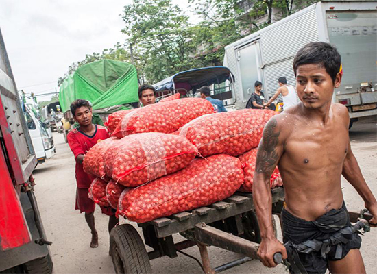 Workers moving bags of onions in Yangon. [Nyan Zay Htet/The Myanmar Times]