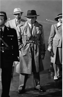 """1942년 개봉, 1944년 제16회 아카데미 최우수 작품상을 수상한 영화 """"카사블랑카""""에서 주인공 험프리 보가트(Humphrey Bogart)는 시종일관 트렌치 코트를 입고 있었다. 사진은 영화 """"카사블랑카""""의 한 장면. 가운데 중절모에 트렌치 코트를 입고 있는 이가 험프리 보가트이다."""