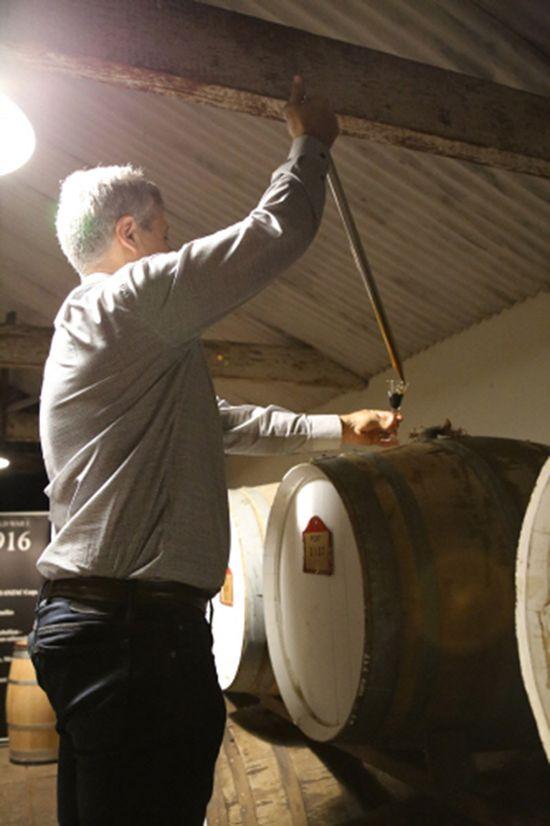 와이너리 안내자가 오크통 사이를 거닐며 방문객이 태어난 해의 와인을 뽑아 준다.