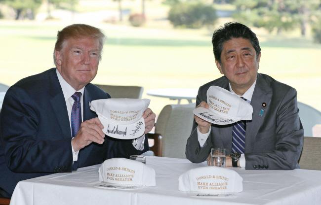 도널드 트럼프 미국 대통령(왼쪽)과 아베 신조(安倍晋三) 일본 총리가 5일 사이타마(埼玉) 현 가스미가세키(霞が關)CC에서 오찬을 하기에 앞서 함께 서명한 모자를 들어 보이고 있다. (연합뉴스)