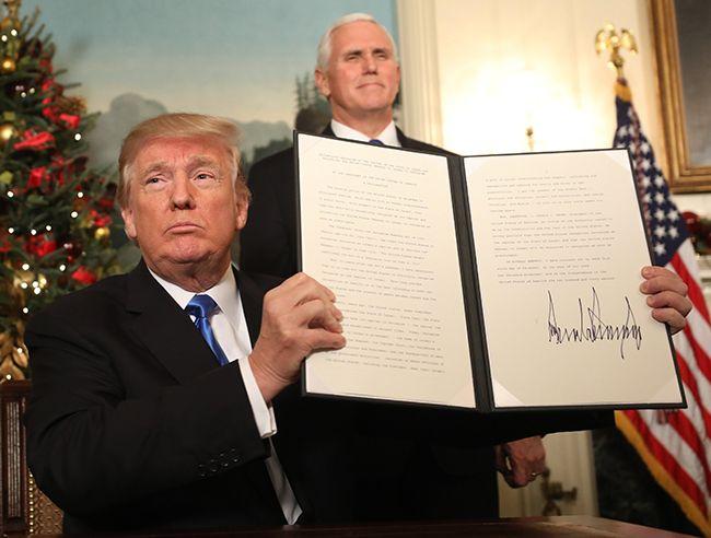 6일(현지시간) 도널드 트럼프 미국 대통령(앞쪽)이 백악관에서 마이크 펜스 미국 부통령(뒤쪽)이 지켜보는 가운데 예루살렘을 이스라엘 수도로 공식 인정한다는 선언문에 서명한 뒤 들어 보이고 있다. /사진=EPA·연합뉴스