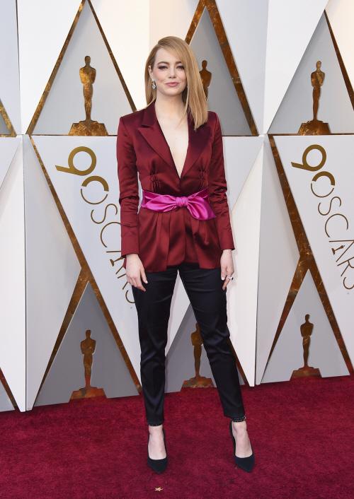 엠마 스톤이 드레드 대신 바지 차림으로 레드 카펫에 서고 있다.