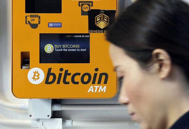 홍콩에 한 여성이 비트코인 ATM 앞을 지나가는 모습. /사진=AP