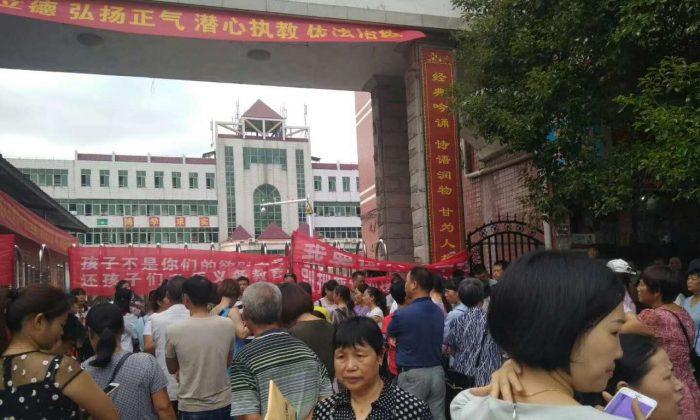 지난 1일 중국 중부 후난성 레이양시의 한 학교 앞에 운집한 시위대가 시 정부의 강제전학 조치에 반대하는 플래카드를 내걸고 농성하고 있다.