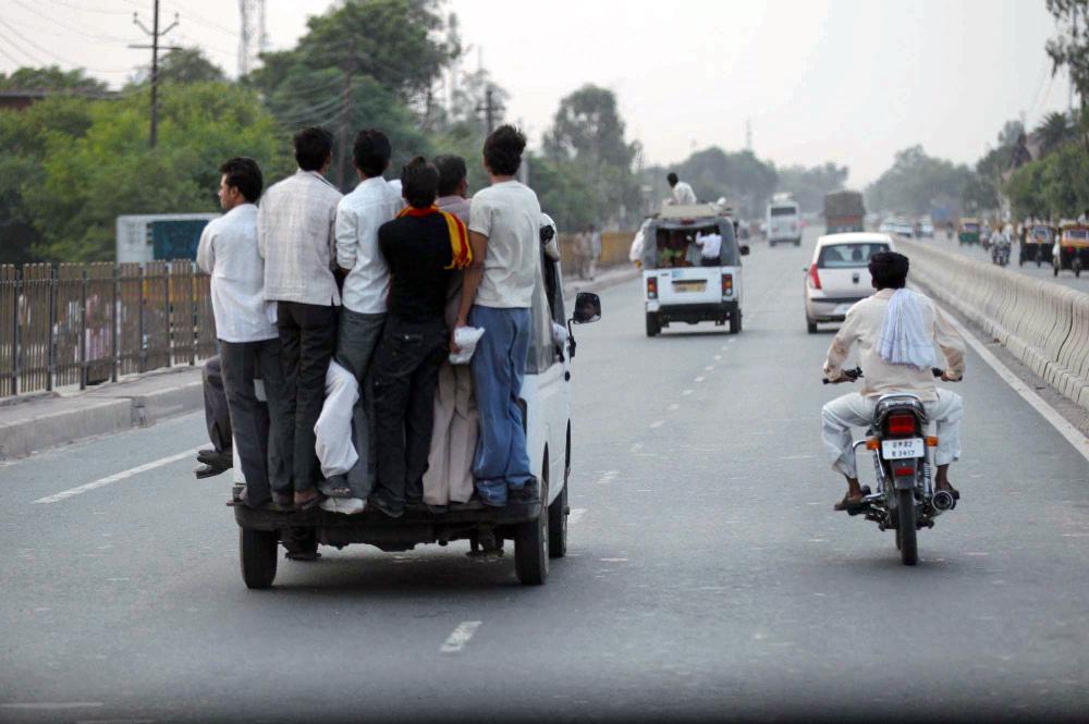자동차 뒤편에서 난간을 잡고 이동하는 인도인들.