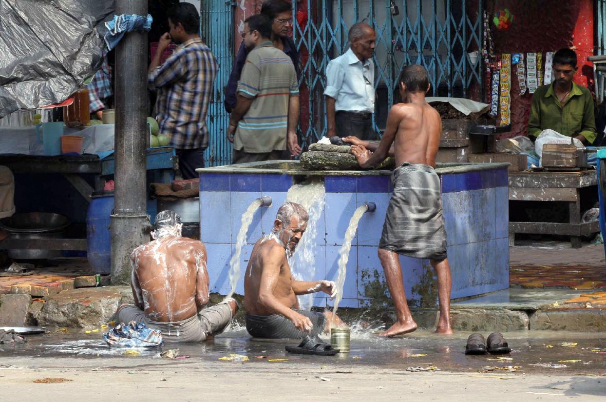 길거리 옆의 우물가에서 목욕하는 인도 남성들.