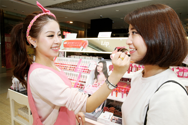싱가포르 에뛰드하우스 부기스 매장에서 직원이 고객에게 립스틱을 발라주고 있다.