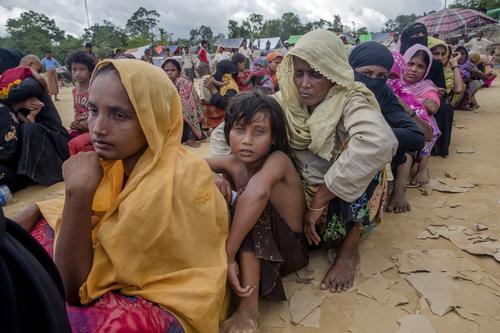 미얀마군의 탄압을 피해 국경을 넘어 방글라데시로 탈출한 이슬람계 소수민족 로힝야족 난민들이 난민캠프에서 음식물을 배급받기 위해 줄지어 앉아서 기다리고 있다. [AP연합뉴스]
