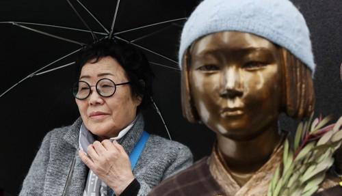 5일 오후 서울 종로구 옛 일본대사관 앞에서 열린 일본군성노예제 문제해결을 위한 제 1277차 정기 수요시위에서 이용수 할머니가 소녀상 뒤에 우산을 쓴 채 앉아있다. [사진=연합뉴스]
