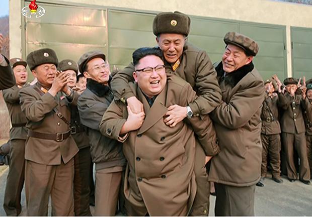 김정은 북한 노동당 위원장이 지난 18일 서해위성발사장에서 신형 고출력 로켓엔진 지상분출시험을 참관한 뒤 국방과학·기술 책임자로 추정되는 관계자를 등에 업고 있는 사진을 조선중앙TV가 19일 내보냈다. [사진=연합뉴스]