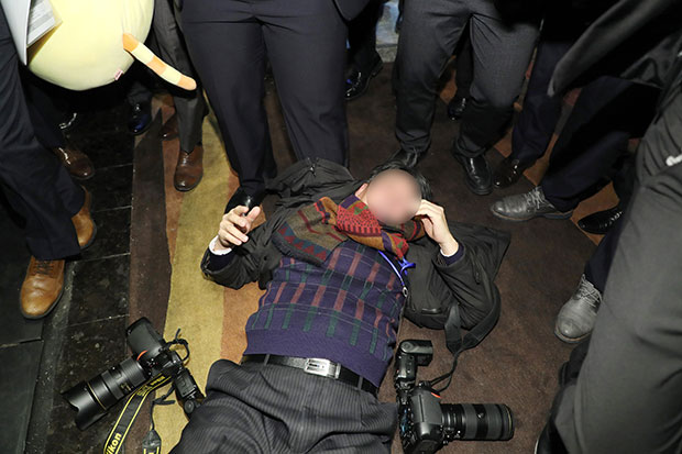 """14일 오전 문재인 대통령 국빈방문 행사를 취재하던 한국의 한 사진기자가 베이징 국가회의 중심 B홀에서 중국 측 경호 관계자에게 일방적으로 폭행 당해 쓰러져 있다. """"한·중 경제·무역 파트너십 개막식 """"에서 스타트업관 이동 중에 폭행당했다.[사진=연합뉴스]"""