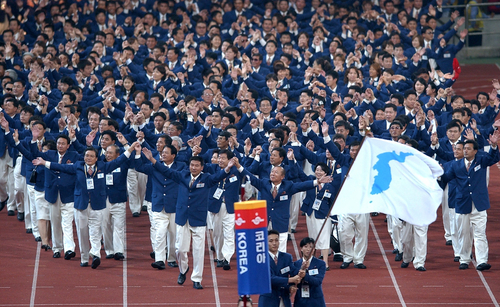 2002년 9월 29일 부산아시안게임 개막식에 공동기수 황보성일(한국 남자핸드볼)과 리정희(북한 여자축구)가 흰바탕에 파란 색깔의 한반도기를 들고 입장하고 있다. [사진=연합뉴스]