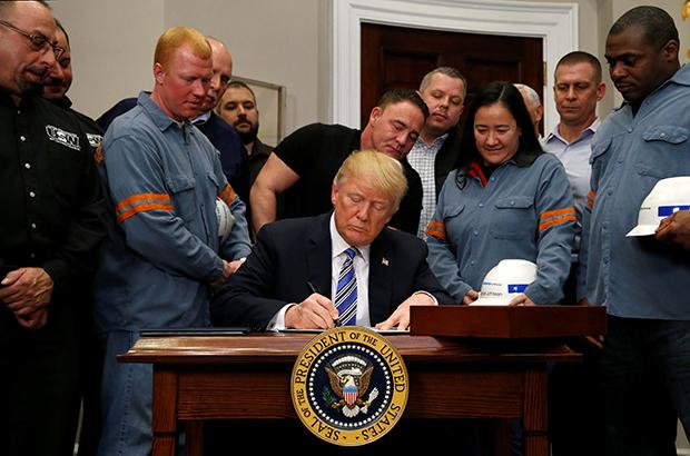 """도널드 트럼프 미국 대통령이 8일(현지시간) 자국산업 보호를 위해 한국산 등의 수입 철강과 알루미늄에 각각 25%, 10%의 고율 관세부과를 강행했다. 캐나다와 멕시코산만 관세 조치 대상국에서 제외됐다. 사진은 이날 백악관에서 철강 업계 노동자와 노조 인사들이 참석한 가운데 트럼프 대통령이 """"미 무역확장법 232조""""를 근거로 관련 철강·알루미늄 규제조치 명령서에 서명하는 모습.[사진=연합뉴스]"""