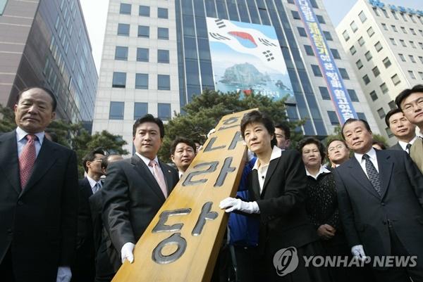 2004년 박근혜 전 대통령이 한나라당 비대위원장 당시 당 현판을 천막당사로 옮기고 있다. [사진=연합뉴스]