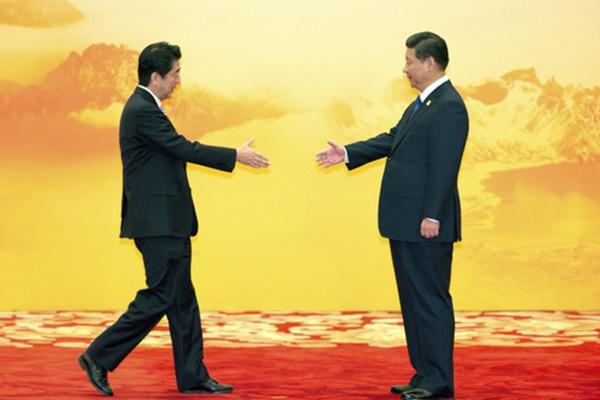 아베 신조 일본 총리(왼쪽)와 시진핑 중국 국가주석이 2014년 11월 중국 베이징에서 열린 역내 경제회의에서 만나 악수를 나누고 있다. 아베 총리는 4일(현지시간) 시 주석과 사상 처음으로 전화 통화했다. [사진=연합뉴스]