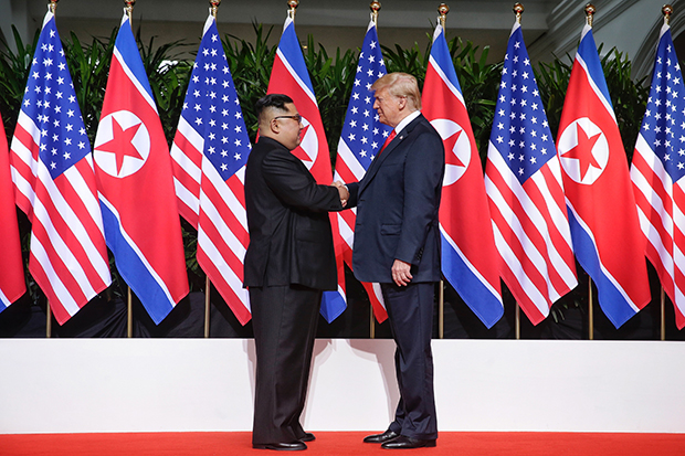 역사적 첫 북미정상회담이 열린 12일 오전 싱가포르 센토사 섬 카펠라호텔에서 미국 도널드 트럼프 대통령과 북한 김정은 국무위원장이 악수하고 있다. [싱가포르 통신정보부 제공=연합뉴스]