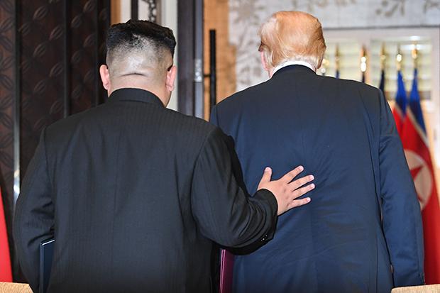 역사적 첫 북미정상회담이 열린 12일(현지시간) 싱가포르 센토사 섬  카펠라호텔에서 미국 도널드 트럼프 대통령(오른쪽)과 북한 김정은 국무위원장이 공동합의문에 서명을 마친 뒤 나란히 서명식장을 빠져나가고 있다. 이때 김 위원장이 트럼프 대통령의 등에 잠시 손을 올리자 트럼프 대통령도 곧이어 같은 동작으로 친근감을 표시했다.[사진=연합뉴스]