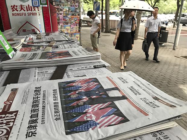 역사적 첫 북미정상회담이 열린 12일(현지시간) 중국 베이징 거리의 신문가판대에 북미정상회담 관련 기사가 1면에 실린 신문들이 놓여 있다.[사진=연합뉴스]