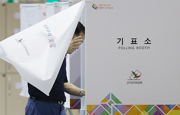 제7회 전국동시 지방선거 투표일인 13일 오후 서울 서대문구 홍제배드민턴장에 마련된 홍제제3동제3투표소에서 한 시민이 기표소로 들어가고 있다.[사진=연합뉴스]