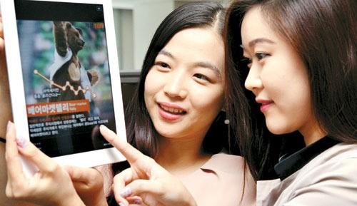 직장인들이 10일 오전 사무실에서 태블릿PC로 페이스북에 접속해 `매경TEST 하루 한 스푼 최신 경제 상식`을 보며 대화를 나누고 있다. <김재훈 기자>