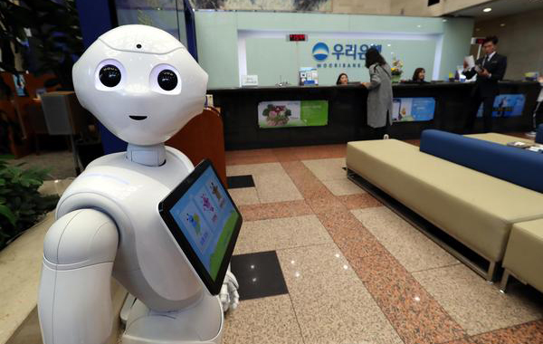 """How may I help you?"" Robot Pepper put into service on Wednesday greets customers at Woori Bank's headquarters in central Seoul. The bank plans to expand the use of robots for customer service in its branches across the nation. [photo by Lee Choong-woo]"