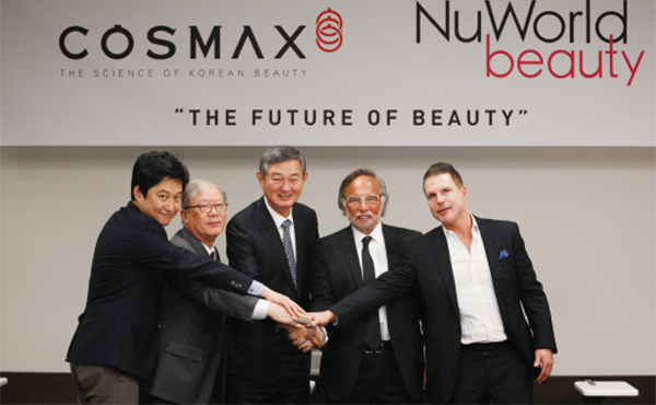 Lee Kyung-soo, chairman and chief executive of Cosmax, center, poses with Stu Dolleck, president of NuWorld Beauty, second from right, and Jonathan Rosenbaum, chief executive of NuWorld Beauty, far right, after signing an acquisition deal at Cosmax headquarters in Pangyo, Gyeonggi, on Monday. [Photo provided by Cosmax Inc.]