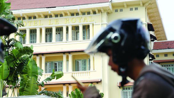 A motorist passes in front of Phnom Penh's Hotel Le Royal in Phnom Penh.