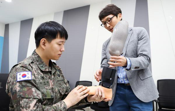 Army Staff Sgt. Kim Jung-won, left, is pictured talking about a commercial prosthetic leg. Kim participated in the robotic prosthesis project from its development phase. [Photo by Korea Institute of Machinery & Materials]