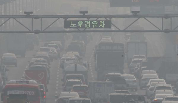A vehicle makes its way on the Gangbyeon Expressway below a surveillance camera installed to monitor old diesel cars near the Gayang Bridge in western Seoul on Sunday when anti-dust reduction measures are enforced in many parts of the country including Seoul and its surrounding areas. [Photo by Lee Chung-woo]