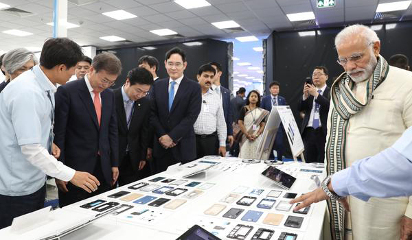 South Korean President Moon Jae-in tours around Samsung Electronics Co.'s new smartphone manufacturing plant in Noida, India, on July 9, last year, with Indian Prime Minister Narendra Modi and company vice chairman Jay Y. Lee. [Photo by Joint Press Corps.]