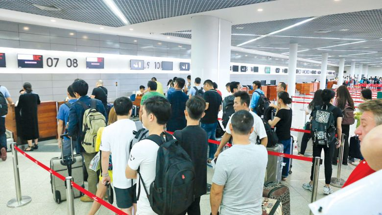 Passengers queue at the Phnom Penh International Airport for their 9C 8534 flight to Shanghai via Spring Airlines on July 10 last year. HENG CHIVOAN