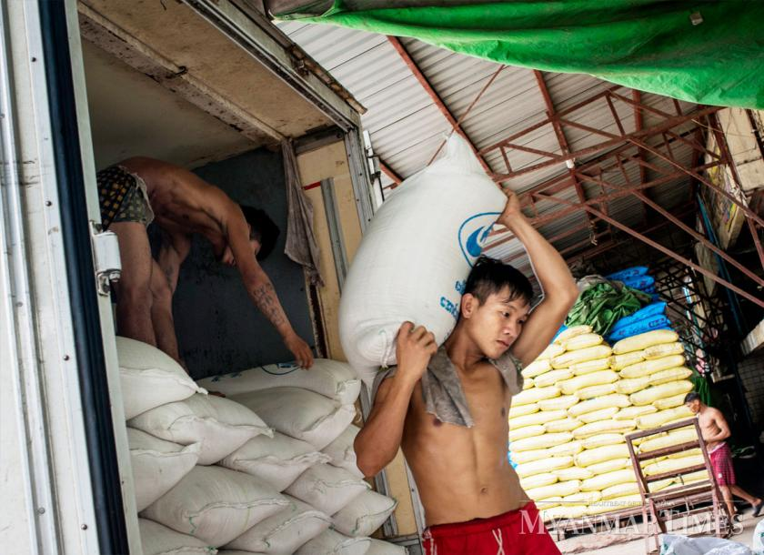 A worker hauls bags of rice in Yangon. Nyan Zay Htet/The Myanmar Times