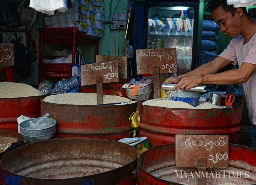 A vendor measures rice at a shop in Yangon. Aung Htay Hlaing/The Myanmar Times
