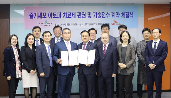 SK Bioland's CEO Lee Geun-sik (left in the center) and KangStem Biotech CEO Lee Tae-hwa hold their agreement during a photo session held in Seoul on Monday. [Photo by SK Bioland]