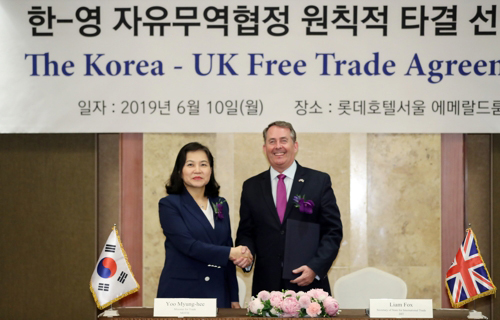 S. Korean Trade Minister Yoo Myung-hee (left) and Liam Fox, the U.K. international trade secretary, pose for a photo during a ceremony on June 10, 2019. [Photo by the Ministry of Trade, Industry and Energy]