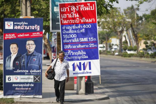 A man walks past a signboard listing Pheu Thai Party policies during the election campaign in March. - Photo by Varuth Hirunyathep